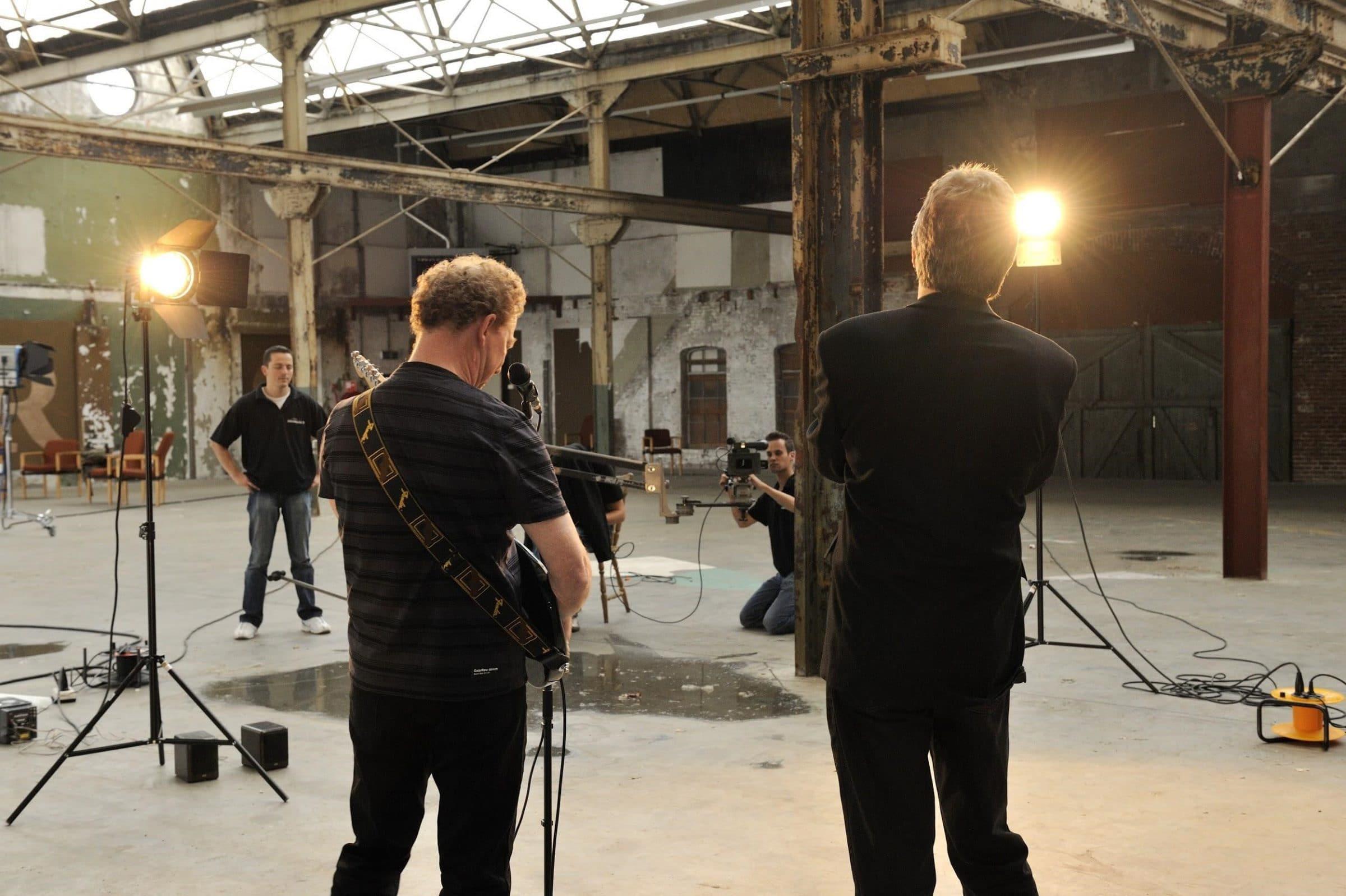 De muzikanten op de voorgrond. De crew aan het werk op set.